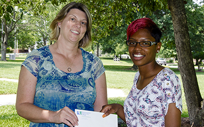 RCC student Kayla Gordon, at right, accepts a check for $500 toward her educational expenses from Cristal Harper of the Warsaw/Richmond County Chamber of Commerce.