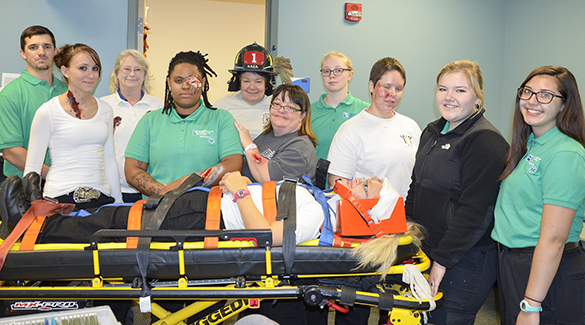 Sierra Cannon of Middlesex County is pictured lying on the stretcher. Standing, left to right, are Nicholas Yarkey, Gloucester County; Kendi Kenyon, Mathews County; lab instructor Jennifer Foster; Emonya Darby, Richmond County; EMT program head Ellen Vest; Kimberly Marrin-Fountain, Middlesex County; Victoria Mason, King George County; Laura Stephan, Hampton; Abigail Hylton, Essex County; and Ali Sydnor, Westmoreland County.