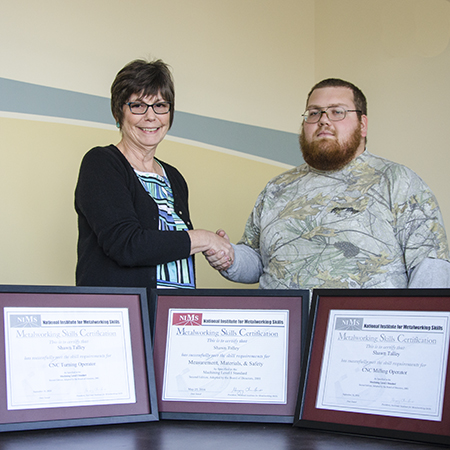 RCC career coach Constance Peay, at left, congratulates student Shawn Talley on earning three skill certifications from the National Institute of Metalworking Skills.