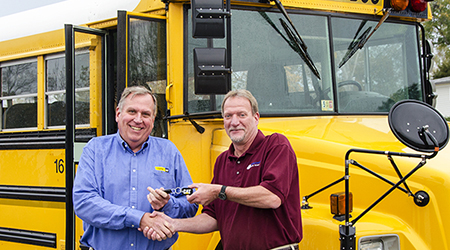 At left, Bill Reinholtz of Carter Machinery Company, Inc., has recently delivered a donated 2001 Thomas Freightliner bus to the Bridging Communities Regional Career and Technical Center. Diesel technology instructor Steven Patt (right) will use it in his classes.