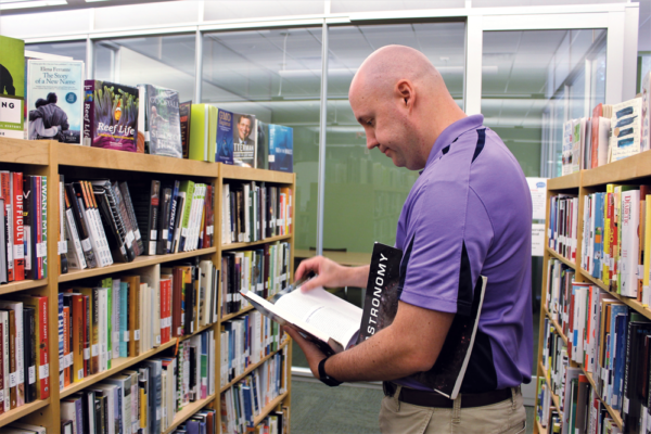 Dr. Brent reading in the RCC library with an Astronomy book under his arm