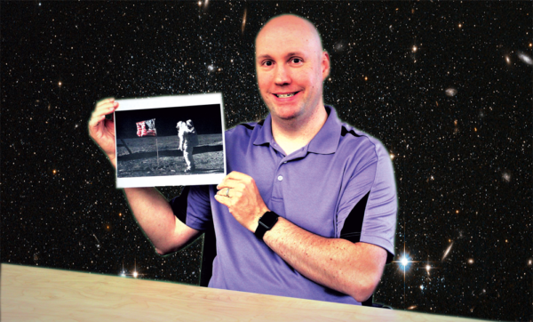 Dr. Brent holding a photo of the moon landing, sitting in front of a background of stars.