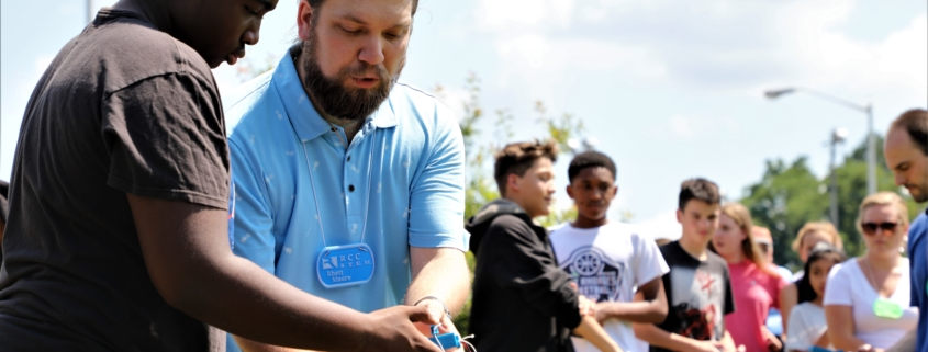 Rhett, an instructor, shows a child how to launch a rocket