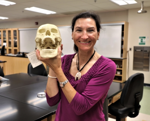 Sarah smiles and poses with a skeleton head, its mouth open