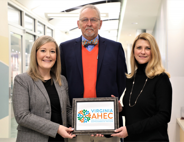 Stacie Wind and Dr. Charles Smith stand with Dr. Shannon Kennedy, RCC President.